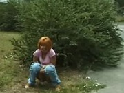 Red head lady taking a pee outdoors